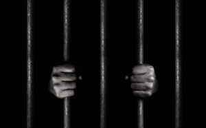 man behind bars showing criminal accountability