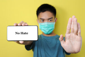 Young asian man wearing protect mask doing stop gesture to stop anti-asian hate crimes